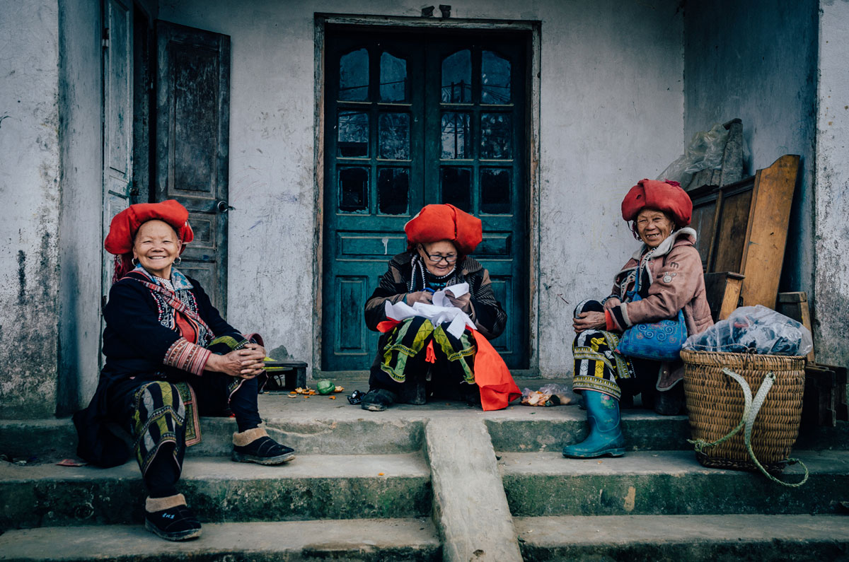 Thress Ta Phin - Red Dao ladies in front of a house with green door
