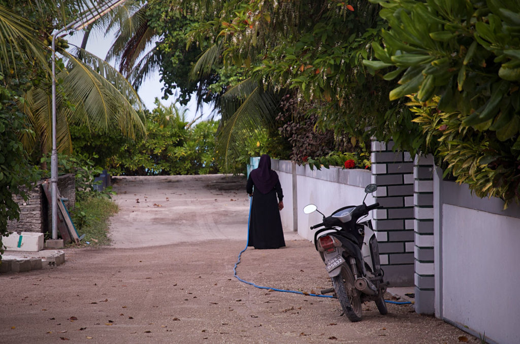 Woman watering her plants - Maldives