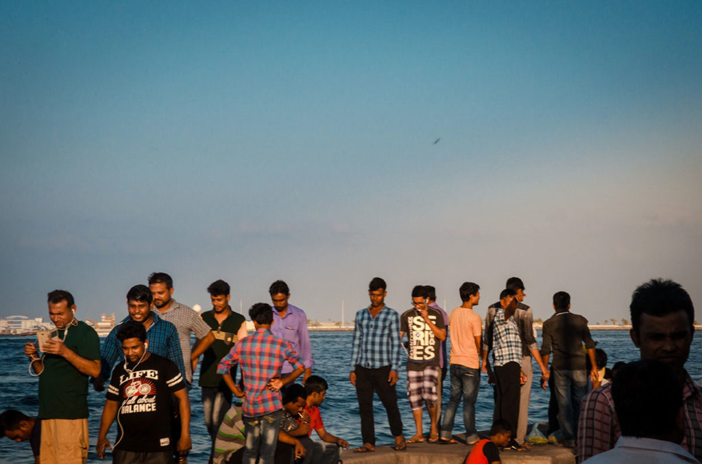 Men on a wall by the water - Malé