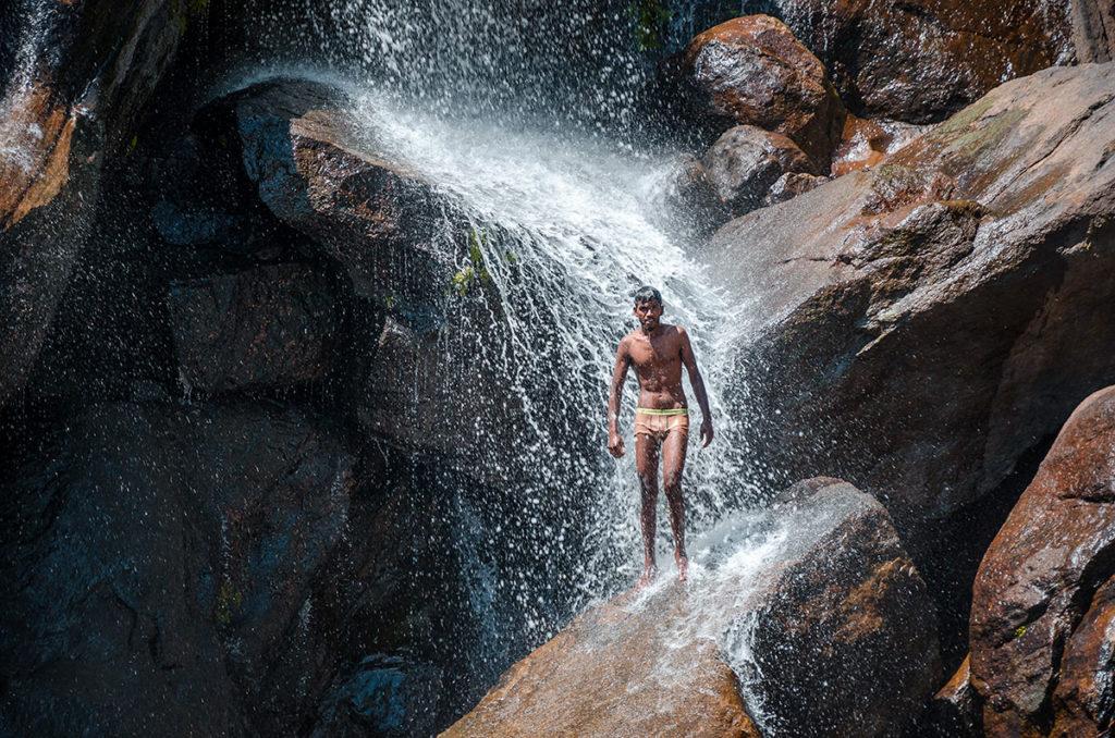 Young man bathing in the falls - Sri Lanka