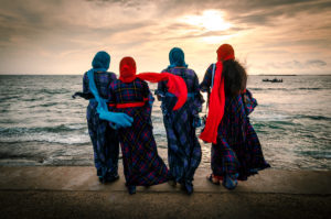 Four women with scarves facings the beach