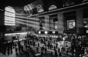 Commuters at Grand Central Station illuminated by the natural light from a huge window