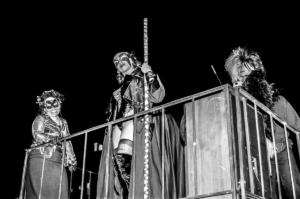 Three ladies on a balcony during a New York Halloween celebration