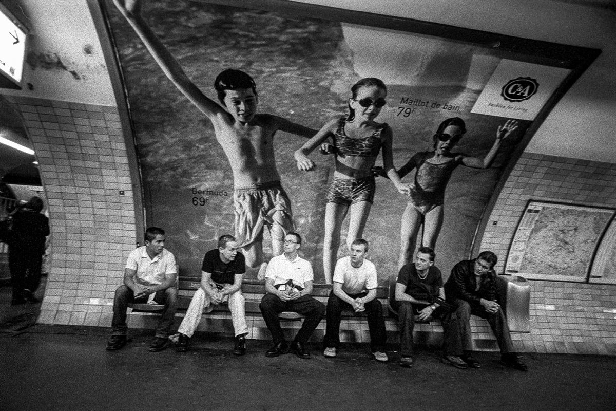 Men sitting at a metro station in Paris